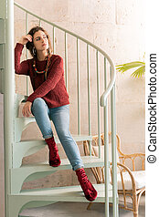 Beautiful dark-haired woman sitting on stairs in nice restaurant