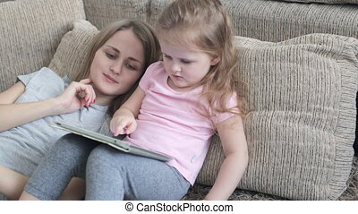 Beautiful daughter playing with tablet