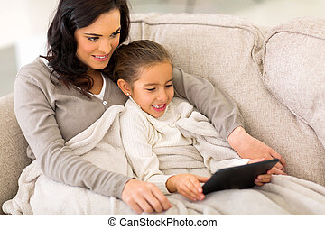daughter using tablet computer with her mother