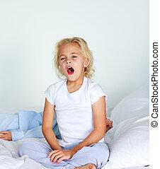 Beautiful daughter yawning in bed