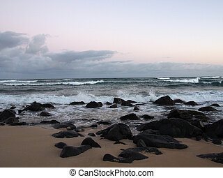 Beautiful Dawn over the ocean with waves crashing into rocks along beach