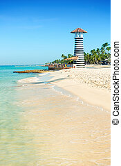 Beautiful day at sea. White sand, tropical palm trees and lighthouse on sandy shore