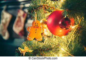 Beautiful decorated Christmas tree with baubles and garland decorated gingerbread men on the new-year background with fireplace and socks. The idea for postcards. Soft focus. Shallow DOF