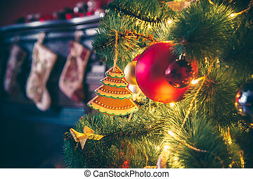 Beautiful decorated Christmas tree with baubles and garland decorated gingerbread, on the new-year background with fireplace and socks. The idea for postcards. Soft focus. Shallow DOF