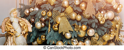 Beautiful decorated golden Christmas tree in luxury classic interior.