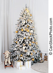 Beautiful decorated golden Christmas tree in luxury white classic interior.