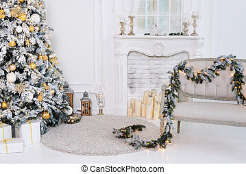 Beautiful decorated golden Christmas tree in luxury white classic interior with fireplace and sofa.
