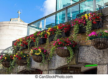 Beautiful decoration with flowers on an old stone wall of a building on the Trinity Square in London
