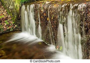 Beautiful decorative stone waterfall pond in garden