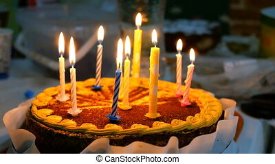 Beautiful delicious birthday cake with burning candles is on kitchen table.