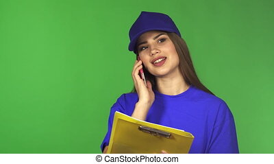 Beautiful delivery woman talking on the phone holding a clipboard
