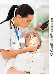 dermatologist inspecting middle aged patient's skin -...