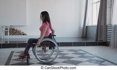 Adult woman in wheelchair spending time at home and looking...