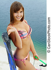 Portrait of teenage girl in bikini holding scubadiving equipment