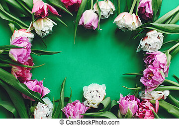 Beautiful double peony tulips frame flat lay on green paper, space for text. Happy mother's day. International women's day. Hello Spring. Stylish Floral Greeting card