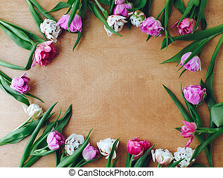 Beautiful double peony tulips frame flat lay on wooden table, space for text. Colorful pink and purple tulips. Happy mother's day. International women's day. Hello Spring. Floral Greeting card