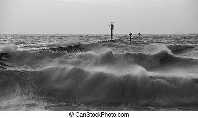 Beautiful dramatic black and white stormy landscape image of waves crashing onto beach at sunrise