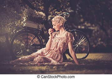Beautiful dreaming blond retro woman with an apple and bicycle behind her
