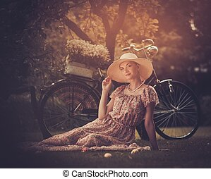 Beautiful dreaming blond retro woman with bicycle behind her