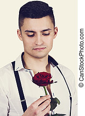 Beautiful dreamy guy with a rose
