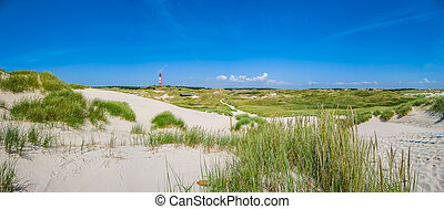 Beautiful dune landscape with traditional lighthouse at North Sea