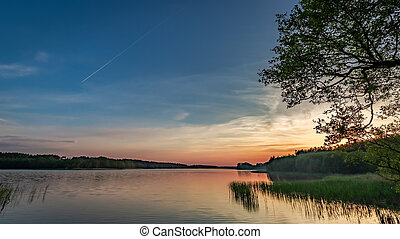 Beautiful dusk at the summer lake with dynamic clouds