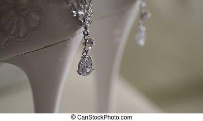 Beautiful earrings and white womens shoes closeup