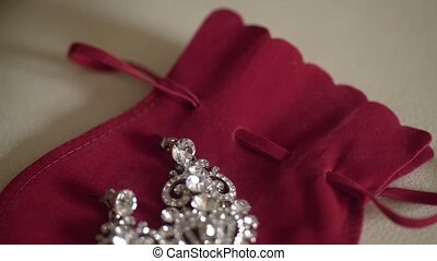 Beautiful earrings on red bag indoors