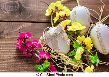 Beautiful Easter eggs with flowers on the wooden background