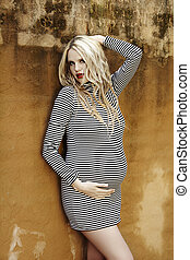 Beautiful eight months pregnant blond woman with curly hair in a black and white stripes fashion mini dress against a grunge wall background .