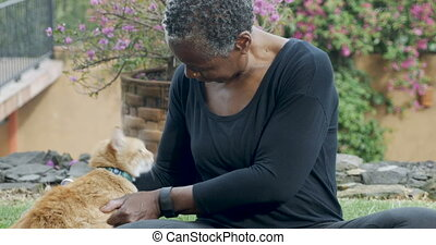 Beautiful elderly black woman petting her orange cat with love outside