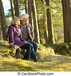 Beautiful elderly couple embracing and enjoying life in the forest at sunset. couple of grandparents embracing