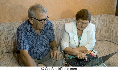 Beautiful elderly couple learns to work on a laptop