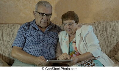 Beautiful elderly couple looking photos on your tablet.