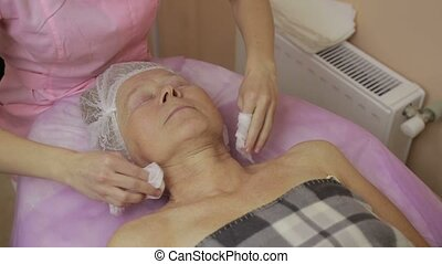 Beautiful elderly woman having face cleaning - Attractive...