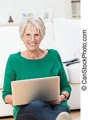 Beautiful elderly woman sitting on the floor