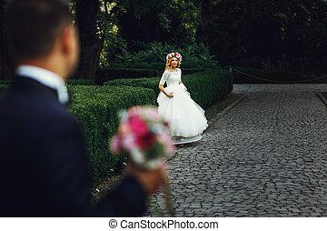 Beautiful elegant blonde bride running towards charming groom outdoors in park