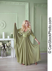 Beautiful elegant blonde woman in fashion long dress posing in modern pistachio interior with decorative elements.
