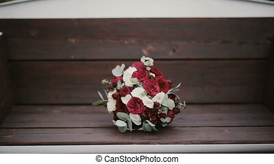 Beautiful elegant bouquet lying on the bench at park. Fresh flower composition on the wooden background.