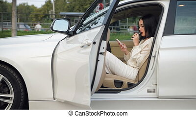 Beautiful elegant business woman is sitting in the car and vaping. Cloud of vapor.