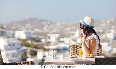 Beautiful elegant girl having breakfast at outdoor cafe