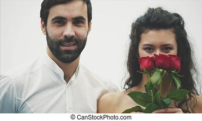 Beautiful elegant guy in a classic shirt with red roses in his hands. Appears on a white background. Gives the roses to his handsome girlfriend and kisses her tenderly. Valentines day.