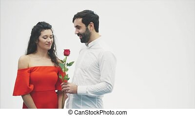 Beautiful elegant guy in a classic shirt with red roses in his hands. Appears on a white background. Gives the roses to his handsome girlfriend and kisses her tenderly