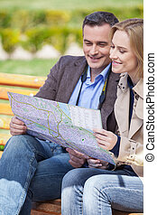 beautiful elegant mid age couple resting outdoors. man holding map and talking to blond woman