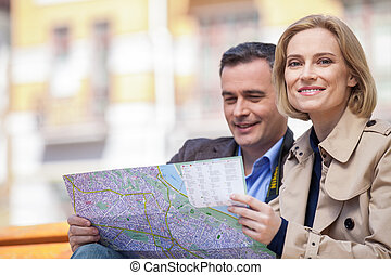 beautiful elegant mid age couple resting outdoors. man holding map while blond woman looking into camera