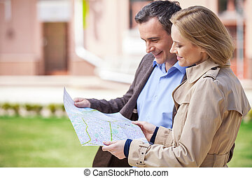 beautiful elegant mid age couple standing outdoors. side view of smiling woman holding map and looking at map