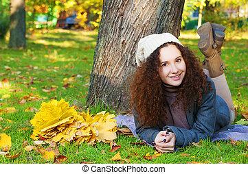 Beautiful elegant woman lying in a park in autumn