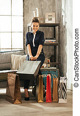 Care-free and elegant brown-haired woman with colourful shopping bags sitting on divan in stylish loft apartment. Good shopping spree makes any woman happy. Luxurious life concept