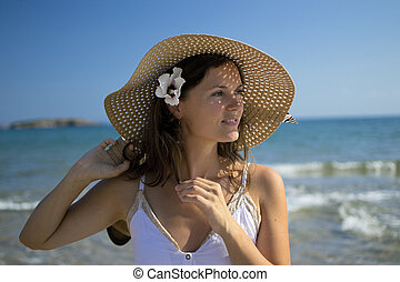 Beautiful elegant young woman by the sea