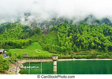 Beautiful emerald mountain lake in Switzerland under low...
